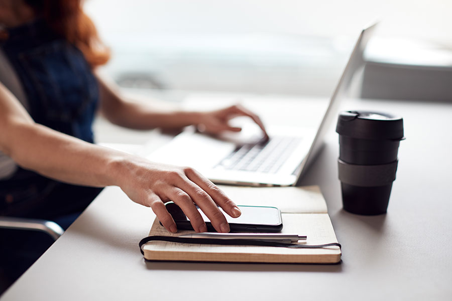 Blog - Woman Working on Laptop while Grabbing Phone on Desk